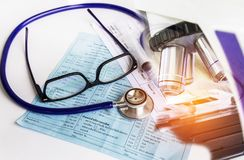 Κλείστε επάνω το στηθοσκόπιο και τα γυαλιά και τη σύριγγα βελόνων σε χαρτί συνταγών διαγραμμάτων αίματος με τον εξοπλισμό μικροσκ Στοκ Εικόνες