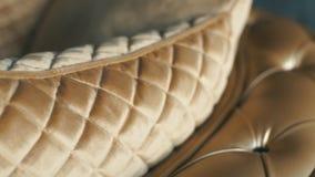 Κλείστε επάνω το σχέδιο δέρματος ενός χρυσού καναπέ πολυτέλειας στο καθιστικό για τη σύσταση υποβάθρου απόθεμα βίντεο