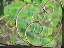 Κλείστε επάνω το σχέδιο της πύλης φρακτών επεξεργασμένου σιδήρου με το υπόβαθρο φύσης στοκ εικόνα με δικαίωμα ελεύθερης χρήσης