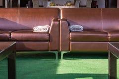 Κλείστε επάνω το σύγχρονο κομψό καφετή καναπέ σαλονιών δέρματος με μάλλινο ρίχνει το κάλυμμα κουβερτών στο βραχίονα Στοκ φωτογραφία με δικαίωμα ελεύθερης χρήσης