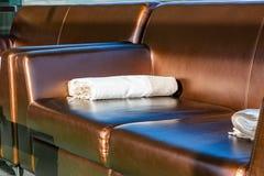 Κλείστε επάνω το σύγχρονο κομψό καφετή καναπέ σαλονιών δέρματος με μάλλινο ρίχνει το κάλυμμα κουβερτών στο βραχίονα Στοκ Φωτογραφίες
