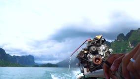 Κλείστε επάνω το των χεριών λεμβούχων ` s που οδηγούν τη βάρκα longtail με μια μεγάλη μηχανή μηχανών φιλμ μικρού μήκους