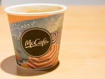 Κλείστε επάνω το φλιτζάνι του καφέ εγγράφου Mcdonald στον πίνακα Εμπορικό σήμα καφέ της Mac στοκ εικόνα με δικαίωμα ελεύθερης χρήσης