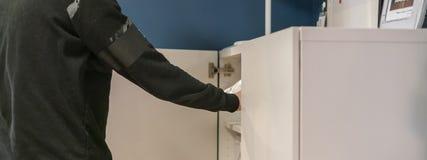 Κλείστε επάνω το χέρι ανοίγει την κρεβατοκάμαρα ραφιών στο σπίτι που ψάχνει για τα πράγματα φ στοκ φωτογραφία με δικαίωμα ελεύθερης χρήσης