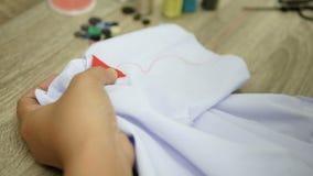 Κλείστε επάνω το χέρι μιας γυναίκας που ράβει ένα κόκκινο σημάδι σε ένα άσπρο πουκάμισο απόθεμα βίντεο