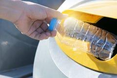 Κλείστε επάνω το χέρι ρίχνοντας το κενό πλαστικό μπουκάλι στα απορρίμματα στοκ φωτογραφία με δικαίωμα ελεύθερης χρήσης