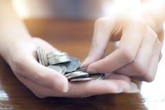 Κλείστε επάνω το χέρι του θηλυκού μετρώντας σωρού των ταϊλανδικών νομισμάτων στην παλάμη της για τα χρήματα κατάθεσης Στοκ Φωτογραφία
