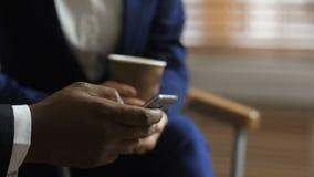 Κλείστε επάνω το χέρι του σκοτεινός-ξεφλουδισμένου ατόμου χρησιμοποιώντας το κινητό τηλέφωνο φιλμ μικρού μήκους