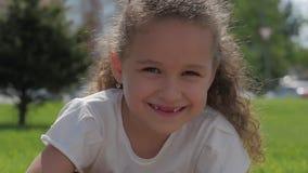 Κλείστε επάνω το χαριτωμένο ευτυχές καυκάσιο χαμόγελο μικρών κοριτσιών πορτρέτου η κάμερα, απολαμβάνοντας τη θερμή ηλιόλουστη ημέ απόθεμα βίντεο