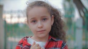 Κλείστε επάνω το χαριτωμένο καυκάσιο κοίταγμα μικρών κοριτσιών πορτρέτου η κάμερα, απολαμβάνοντας τη θερμή θερινή ημέρα στο ηλιοβ φιλμ μικρού μήκους