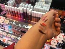 Κλείστε επάνω το χειλικό ελεγκτή δοκιμής βραχιόνων κοριτσιών Α όλο το χρώμα στο κατάστημα ραφιών Maybelline από τη γουλιά στοκ εικόνα με δικαίωμα ελεύθερης χρήσης