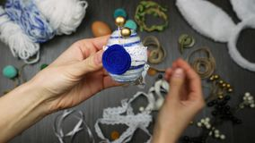 Κλείστε επάνω το χειροποίητο αυγό Πάσχας Διακόσμηση με το νήμα, τις χάντρες, αισθητά και την κορδέλλα Σύγχρονο και απλό σχέδιο φιλμ μικρού μήκους