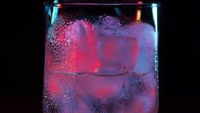 Κλείστε επάνω το χρονικό σφάλμα του πάγου που λειώνει στο γυαλί Μακρο πυροβολισμός ενός κρύου ποτού στο μαύρο υπόβαθρο απόθεμα βίντεο