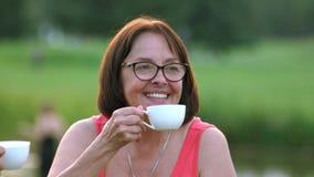 Κλείστε επάνω το όμορφο τσάι κατανάλωσης γυναικών υπαίθρια φιλμ μικρού μήκους
