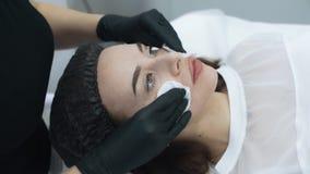 Κλείστε επάνω το beautician καθαρίζει το δέρμα του προσώπου γυναικών πριν από τη διαδικασία, σε αργή κίνηση φιλμ μικρού μήκους