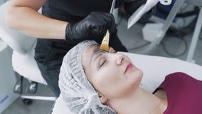 Κλείστε επάνω το cosmetologist εφαρμόζει τη μαύρη μάσκα άνθρακα στο δέρμα του προσώπου γυναικών, σε αργή κίνηση απόθεμα βίντεο