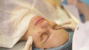 Κλείστε επάνω το cosmetologist καθαρίζει το δέρμα γυναικών με τα υγρά μαξιλάρια βαμβακιού πριν από τη διαδικασία προσοχής προσώπο φιλμ μικρού μήκους