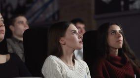 Κλείστε επάνω τριών αρκετά θηλυκών φίλων τρώει popcorn και προσέχει έναν κινηματογράφο στον κινηματογράφο απόθεμα βίντεο