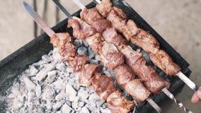 Κλείστε επάνω των ανθρώπινων χεριών που περιστρέφονται το κρέας ψητού στα οβελίδια, σε αργή κίνηση, τρόφιμα οδών απόθεμα βίντεο