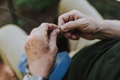 Κλείστε επάνω των αρσενικών χεριών καθορίζοντας το γάντζο ράβδων στοκ φωτογραφία με δικαίωμα ελεύθερης χρήσης