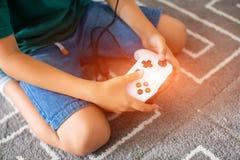 Κλείστε επάνω των αρσενικών χεριών κρατώντας έναν ελεγκτή πηδαλίων παίζοντας ένα τηλεοπτικό πορτρέτο παιχνιδιών στο σπίτι του νεα Στοκ φωτογραφία με δικαίωμα ελεύθερης χρήσης