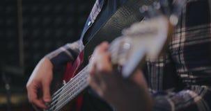 Κλείστε επάνω των αρσενικών χεριών παίζοντας τη βαθιά κιθάρα απόθεμα βίντεο