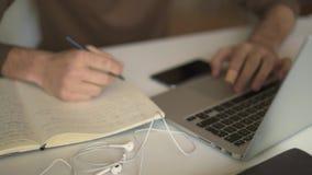 Κλείστε επάνω των αρσενικών χεριών σπουδαστών που κάνουν την εργασία με το lap-top φιλμ μικρού μήκους