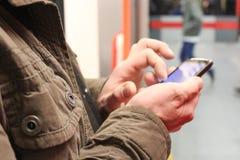 κλείστε επάνω των αρσενικών χεριών χρησιμοποιώντας ένα smartphone στοκ εικόνες