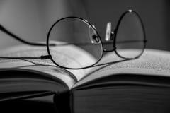 Κλείστε επάνω των γυαλιών βάζοντας σε ένα ανοικτό βιβλίο στοκ φωτογραφία με δικαίωμα ελεύθερης χρήσης