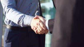 Κλείστε επάνω των επιτυχών επιχειρηματιών που χαιρετούν ο ένας τον άλλον κοντά στο κτίριο γραφείων Δύο νέοι συνάδελφοι που συναντ απόθεμα βίντεο