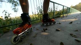 Κλείστε επάνω των ευθύγραμμων ποδιών σκέιτερ κυλίνδρων Πατινάζ στα σκληρά σαλάχια κοχυλιών στο δρόμο γεφυρών λιμνών φιλμ μικρού μήκους