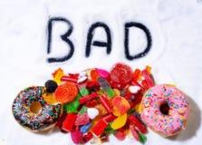 Κλείστε επάνω των ζωηρόχρωμων καραμελών γλυκών donuts με κακό που γράφεται στην άσπρη ζάχαρη στην ανθυγειινή διατροφή παιδιών στοκ εικόνες με δικαίωμα ελεύθερης χρήσης