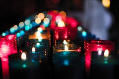 Κλείστε επάνω των ζωηρόχρωμων κεριών σε μια σκοτεινή πνευματική σκηνή Εορτασμός, κηδεία, αναμνηστική Θρησκευτικός συμβολισμός στοκ φωτογραφίες