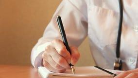 Κλείστε επάνω των θηλυκών χεριών γιατρών ` s, γράφει στο σημειωματάριο απόθεμα βίντεο