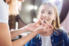 Κλείστε επάνω των θηλυκών χεριών εφαρμόζοντας το κραγιόν στα χείλια κοριτσιών Στοκ Φωτογραφία