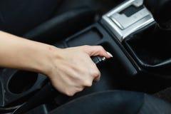 Κλείστε επάνω των θηλυκών χεριών κρατώντας έναν handbrake μοχλό για να κρατήσει το όχημα στάσιμο Το κορίτσι βάζει το αυτοκίνητο σ στοκ εικόνες με δικαίωμα ελεύθερης χρήσης