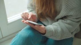 Κλείστε επάνω των θηλυκών χεριών χρησιμοποιώντας το τηλέφωνο στο σπίτι φιλμ μικρού μήκους