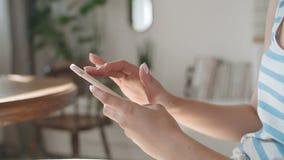 Κλείστε επάνω των θηλυκών χεριών χρησιμοποιώντας το τηλέφωνο στο σπίτι απόθεμα βίντεο