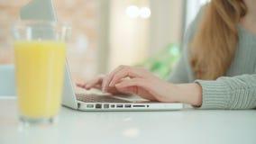 Κλείστε επάνω των θηλυκών χεριών χρησιμοποιώντας το φορητό προσωπικό υπολογιστή καθμένος στον πίνακα απόθεμα βίντεο