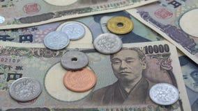 Κλείστε επάνω των ιαπωνικών γεν νομισμάτων που αφορούν το υπόβαθρο γεν τραπεζογραμματίων 1000 και 10000 απόθεμα βίντεο