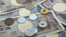 Κλείστε επάνω των ιαπωνικών γεν νομισμάτων που αφορούν το υπόβαθρο γεν τραπεζογραμματίων 1000 και 10000 Έξοχο σε αργή κίνηση fsp  φιλμ μικρού μήκους
