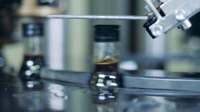 Κλείστε επάνω των καλυμμάτων που παίρνουν τεθειμένων επάνω στα μπουκάλια γυαλιού μηχανικά φιλμ μικρού μήκους