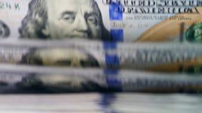 Κλείστε επάνω των λογαριασμών δολαρίων που ρέουν στο μετρώντας μηχανισμό φιλμ μικρού μήκους