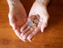 Κλείστε επάνω των νομισμάτων εκμετάλλευσης χεριών της ηλικιωμένης γυναίκας στοκ εικόνα με δικαίωμα ελεύθερης χρήσης