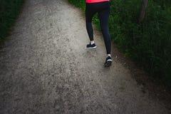 Κλείστε επάνω των ποδιών της νέας γυναίκας που τρέχουν κατά μήκος της πορείας Στοκ Φωτογραφία