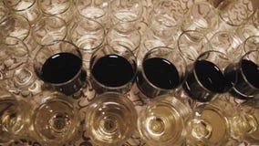 Κλείστε επάνω των ποτηριών του κρασιού σε έναν πίνακα κατά τη διάρκεια μιας δοκιμής κρασιού φιλμ μικρού μήκους