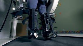 Κλείστε επάνω των σταθεροποιηθε'ντων ποδιών περπατώντας κατά μήκος της μηχανής προσομοίωσης απόθεμα βίντεο