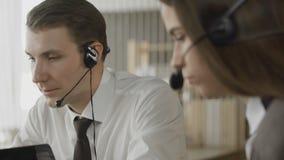 Κλείστε επάνω των χειριστών εξυπηρέτησης πελατών που παίρνουν τις κλήσεις στο πολυάσχολο τηλεφωνικό κέντρο απόθεμα βίντεο