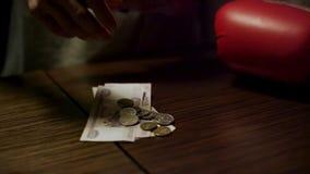 Κλείστε επάνω των χεριών ατόμων κρατώντας ένα ανοικτό πορτοφόλι δέρματος με μερικά νομίσματα μέσα πέρα από έναν παλαιό ξύλινο πίν απόθεμα βίντεο