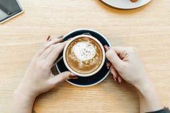 Κλείστε επάνω των χεριών γυναικών κρατώντας το φλιτζάνι του καφέ Τοπ όψη στοκ φωτογραφία
